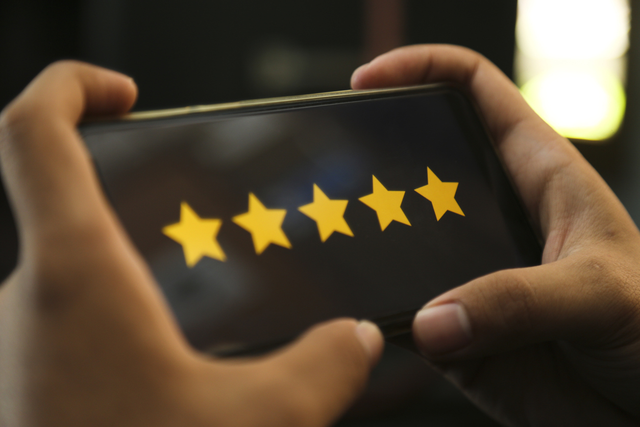 hands showing five stars rating on a smart phone